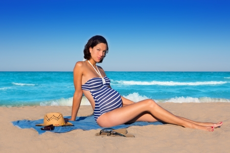 enceinte: Beautiful pregnant woman sitting on blue beach sand in summer vacation
