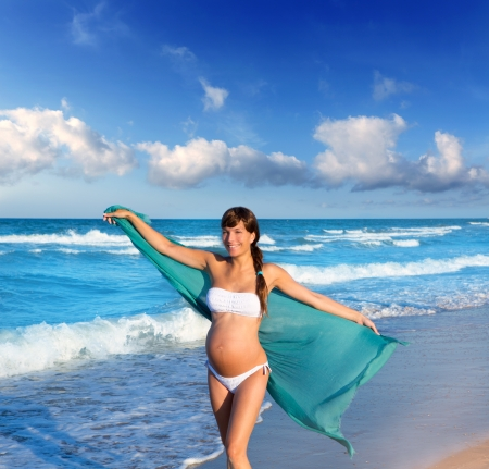 Beautiful pregnant woman walking on blue beach in summer with blowing wind handkerchief photo
