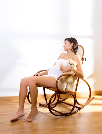 Beautiful pregnant woman sitting on rocker chair with teddy bear photo