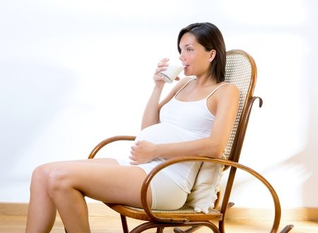 Beautiful pregnant woman drinking milk at home on rocker chair photo