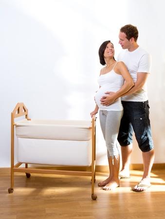 homme enceinte: Couple avec c�lin femme enceinte avec station d'accueil b�b� � la maison Banque d'images