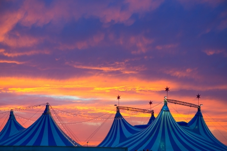 big top: Circus tent in a dramatic sunset sky colorful orange blue with lights