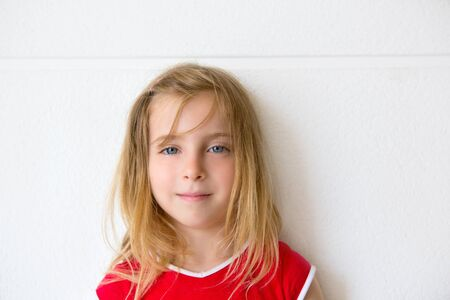 blonde  blue eyes: Blond beautiful kid girl smiling on a white wall portrait