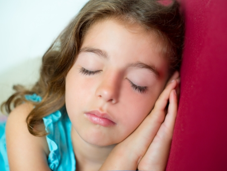 beautiful brunete kid girl sleeping hands together on red sofa photo