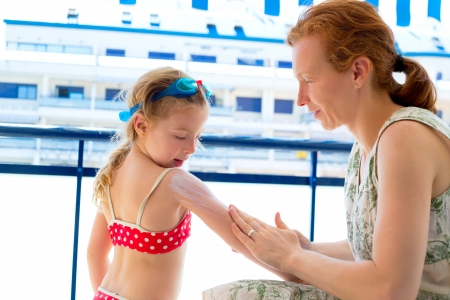 children girl with mother applying sunscreen in summer photo