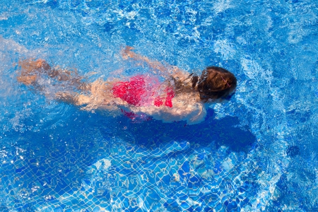 bikini kid girl swimming on blue tiles pool in summer vacation photo