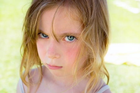 beautiful blonde girl with green eyes: Angry blond children girl portrait looking at camera Stock Photo