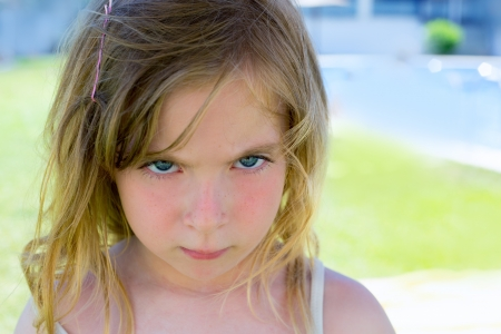 Angry blond children girl portrait looking at camera photo