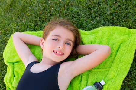 children girl relaxed lying on towel over green grass with water bottle in swimsuit photo
