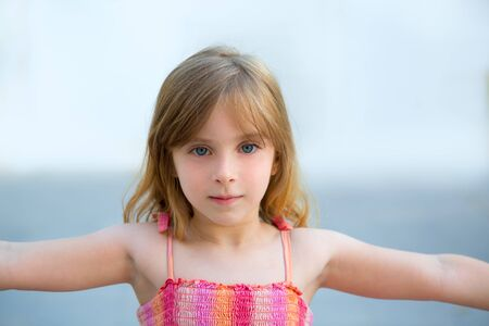Blond kid girl open arms in outdoor with sundress photo