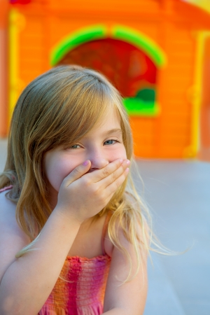 Blond kid girl funny gesture hand in mouth in playground with sundress photo