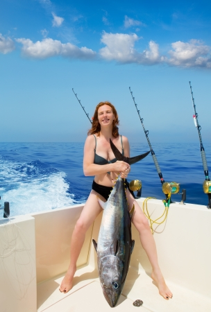 big game fishing: beautiful bikini fisher woman holding big bluefin tuna catch on boat deck