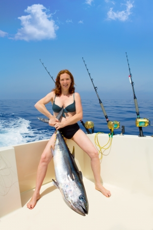 beautiful bikini fisher woman holding big bluefin tuna catch on boat deck photo