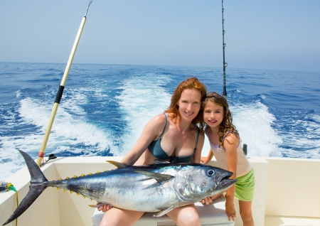 small boat: bikini fisher woman and daughter girl holding big bluefin tuna catch on boat deck Stock Photo