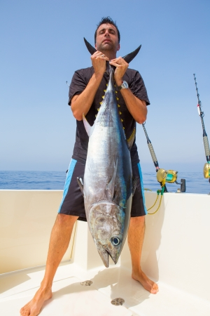 anglers: big Bluefin tuna catch by fisherman on boat trolling posing on deck