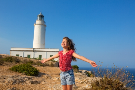 formentera: blue day with kid girl open hands to the wind in la Mola lighthouse of Formentera Stock Photo
