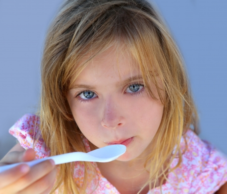 hungry kid: Blue eyes kid girl eating breakfast with spoon portrait