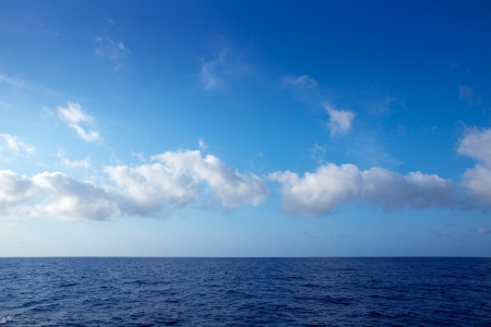 deep sea: cumulus clouds in blue sky over ocean water horizon Stock Photo