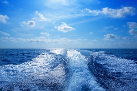 Boat wake speedy prop wash foam in blue sky at Mediterranean photo