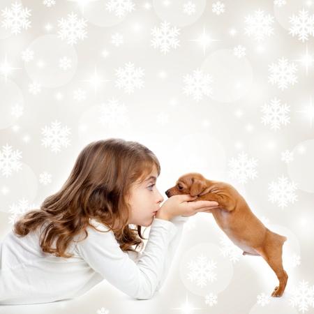 Weihnachten Schneeflocken mit Kindern Mädchen umarmt einen Welpen braune Hund
