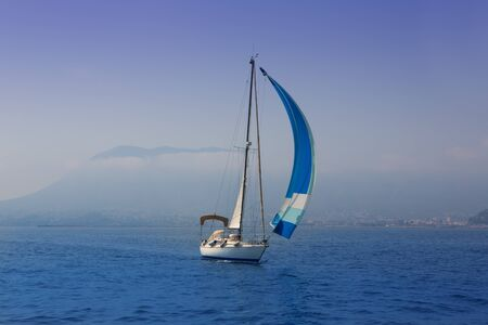 yachting: Blue sea with sailboat sailing in a foggy coast in mediterranean sea Stock Photo