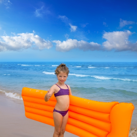 child swimsuit: children kid girl standing in beach shore with orange floating lounge ok hand sign Stock Photo