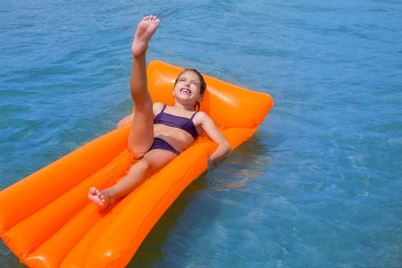 swimsuit: children kid girl playing in beach shore with orange floating lounge
