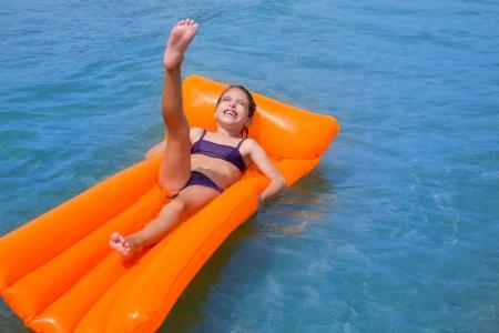 badpak: kinderen kind meisje spelen in strand wal met oranje drijvende lounge Stockfoto