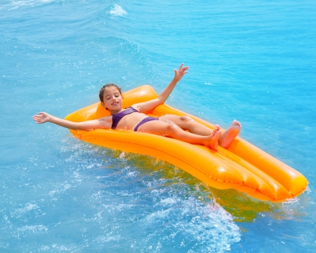 children kid girl playing in beach shore with orange floating lounge
