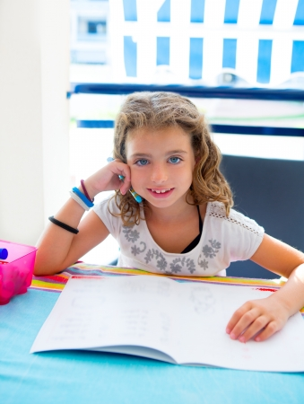 little table: children kid girl smiling with homework in summer holding pencil