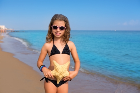 blue beach kid girl with bikini starfish and sunglasses at summer vacations