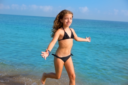 child swimsuit: blue beach kid girl with bikini jumping and running splashing water Stock Photo
