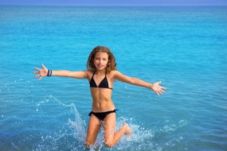 blue beach kid girl with bikini jumping and running splashing water photo