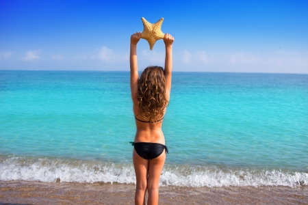 blue beach kid girl with bikini holding starfish looking sea in rear view photo