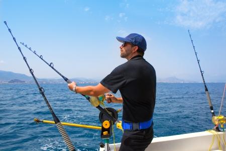 hengelsport: blauwe zee visser in sleepvaartuigen in actie met Downrigger en stang Stockfoto