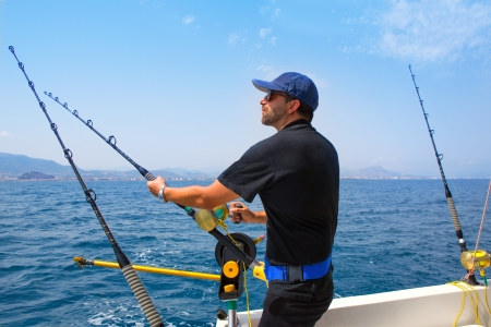 fisherman on boat: blue sea fisherman in trolling boat in action with downrigger and rod