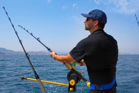 fishing pole: blue sea fisherman in trolling boat in action with downrigger and rod