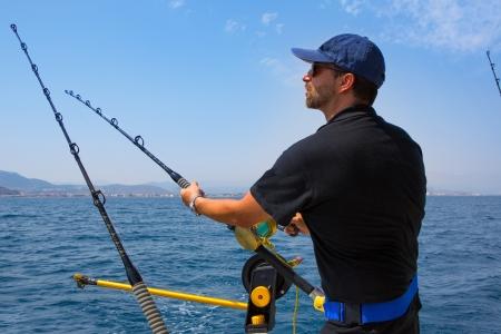 trolling: pescador en el mar azul barco de arrastre en la acci�n con profundizador y varilla