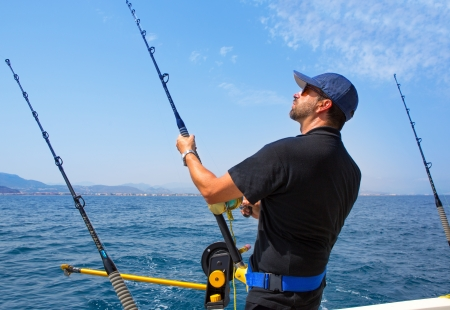 fisherman boat: blue sea fisherman in trolling boat in action with downrigger and rod