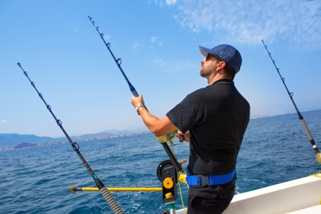 big game fishing: blue sea fisherman in trolling boat in action with downrigger and rod