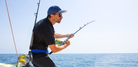 man fishing: blue sea offshore fishing boat with fisherman holding rod in action
