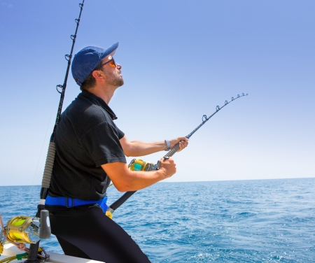 fishing lure: blue sea offshore fishing boat with fisherman holding rod in action