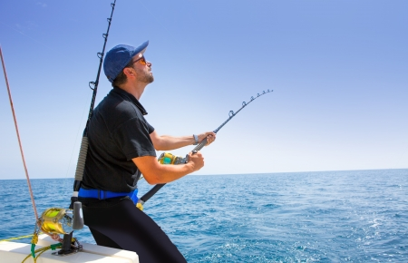 fishing bait: blue sea offshore fishing boat with fisherman holding rod in action