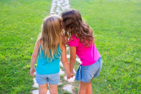 friends sister girls whispering secret in ear in grass garden track park outdoor photo