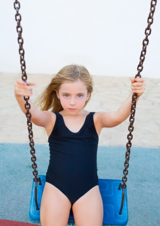 child swimsuit: blond children girl swinging on blue swing in black swimsuit on summer vacations