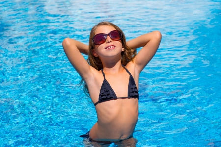 bikini kid girl with fashion sunglasses posing in blue pool photo