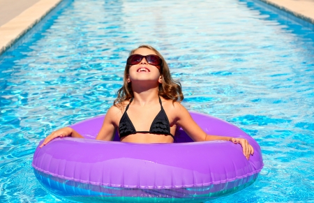 bikini kid girl with fashion sunglasses with purple inflatable pool ring