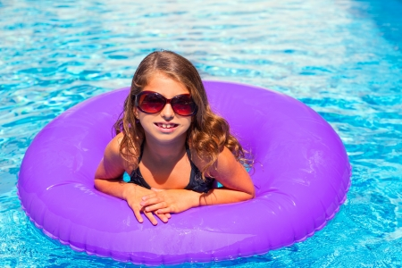 bikini kid girl with fashion sunglasses with purple inflatable pool ring photo