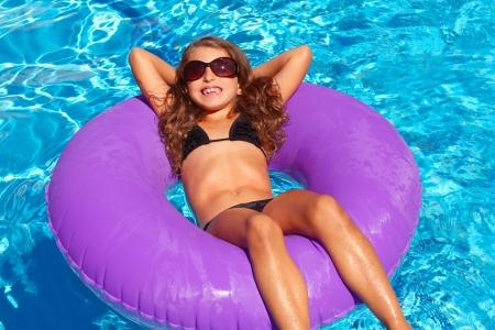 child in bikini: bikini children girl with sunglasses relaxed on purple inflatable pool ring Stock Photo