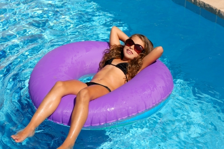 girl with rings: bikini children girl with sunglasses relaxed on purple inflatable pool ring Stock Photo